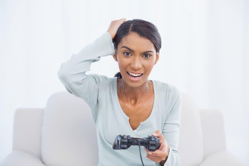 Donna irritata che si siede sul sofà che gioca i video giochi immagini stock libere da diritti