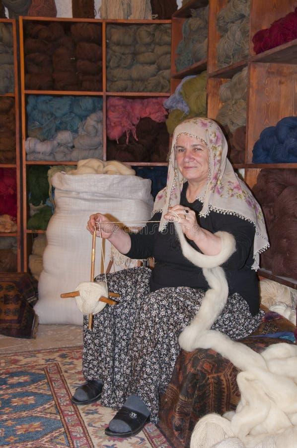 Donna islamica tradizionale che lavora ad una coperta immagine stock