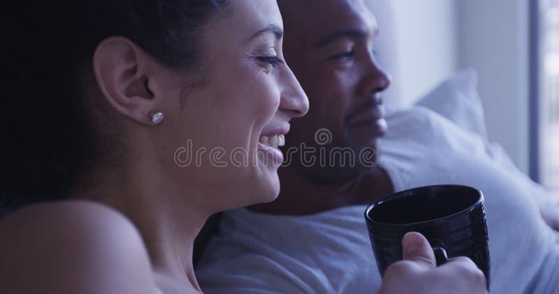 Donna ispana che ride e che sorride mentre bevendo caffè con il ragazzo nero a letto immagine stock