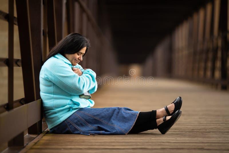 Donna ispana che si siede su un ponte e che tiene la sua bibbia immagine stock libera da diritti