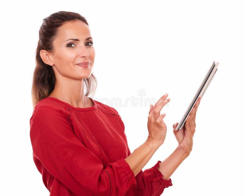 Donna ispanica affascinante che per mezzo del suo pc della compressa fotografia stock