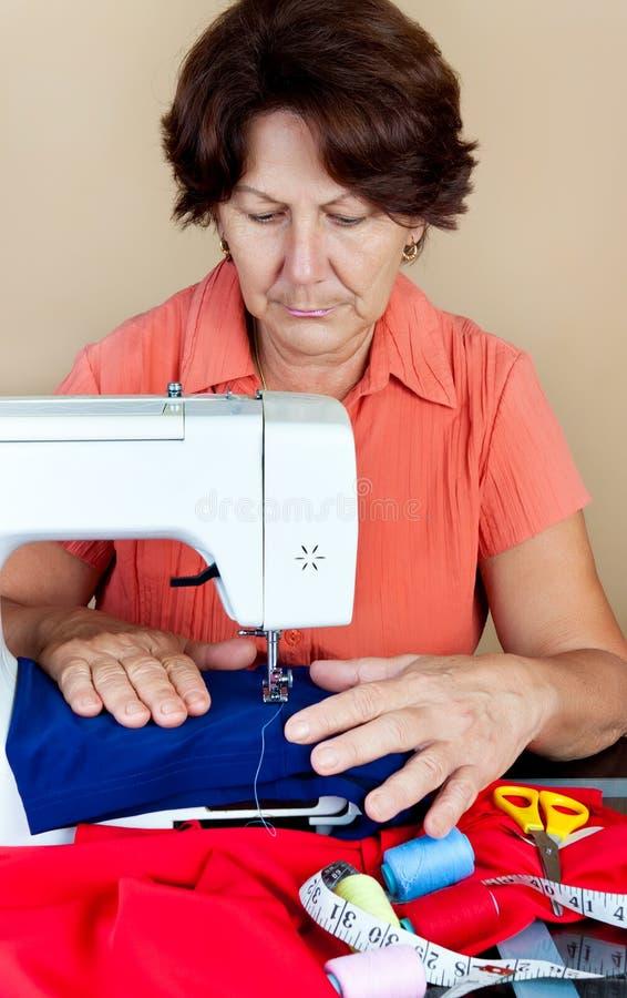 Donna ispanica che lavora ad una macchina per cucire fotografie stock