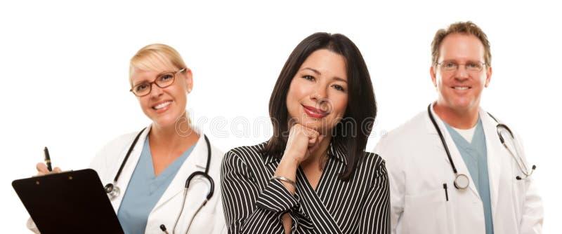 Donna ispanica con il medico e l'infermiera maschii immagine stock libera da diritti