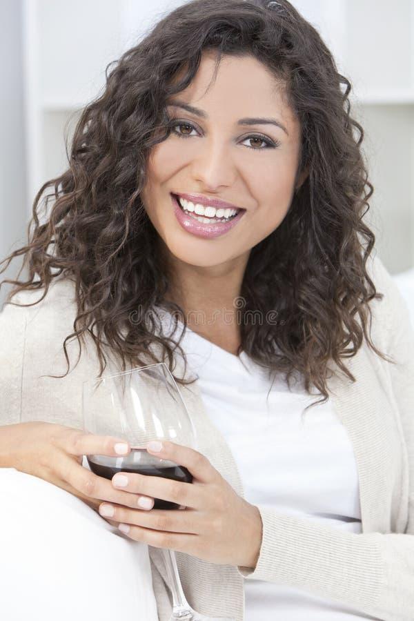 Donna ispanica felice di Latina che beve vino rosso fotografia stock