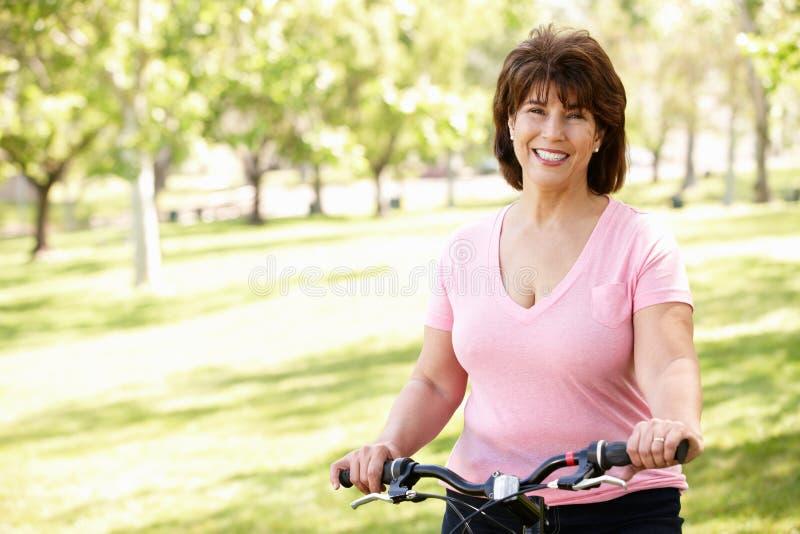 Donna ispanica maggiore con la bici immagini stock