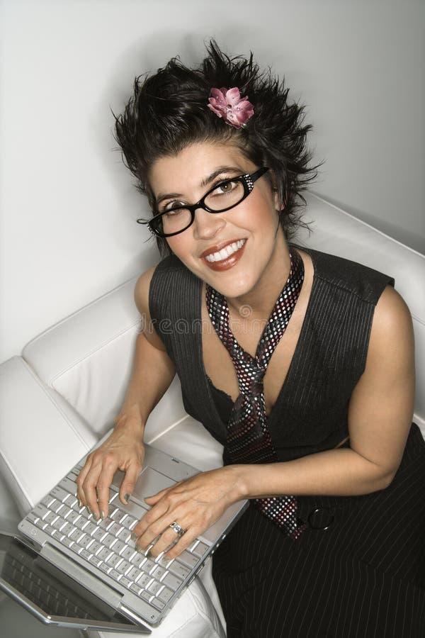 Donna ispanica sul computer portatile. immagini stock