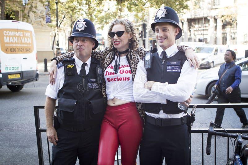 Donna in jeans rossi stretti, maglietta bianca e cappotto macchiato del faux posanti con due poliziotti fotografia stock libera da diritti