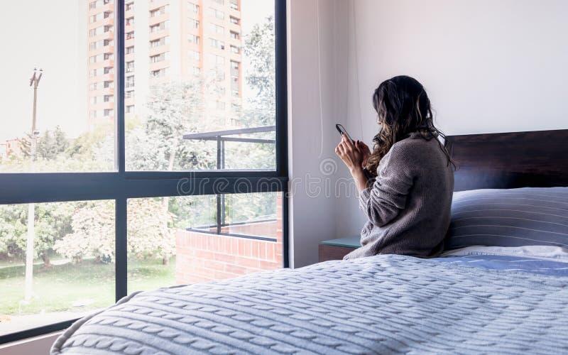 Donna latina che guarda il telefono cellulare nella sua camera da letto, decima foto fotografia stock libera da diritti