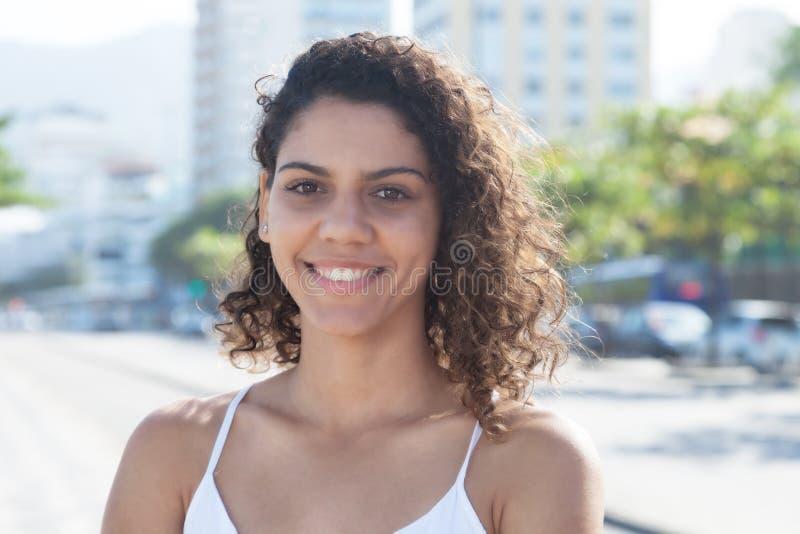 Donna latina sveglia fuori nella città che esamina macchina fotografica fotografia stock libera da diritti