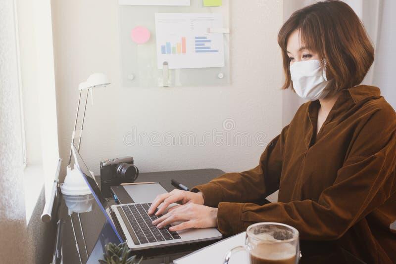 Donna lavora a casa o in remoto per il virus corona o per la pandemia 19 freelancer creativo che lavora e lavora online immagine stock