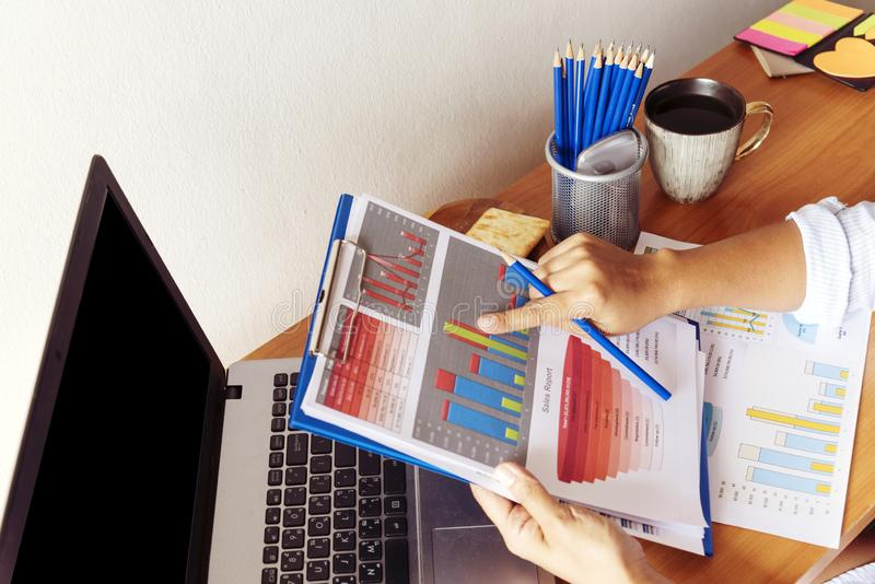 Donna lavoratrice astuta alla sua scrivania con i documenti ed il computer portatile Donna di affari che lavora al lavoro di uffi fotografie stock libere da diritti