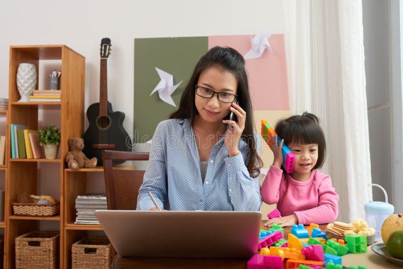 Donna lavoratrice con la ragazza allegra a casa fotografia stock libera da diritti