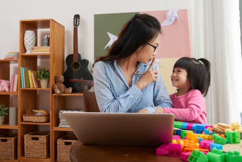 Donna lavoratrice con la ragazza allegra a casa fotografie stock
