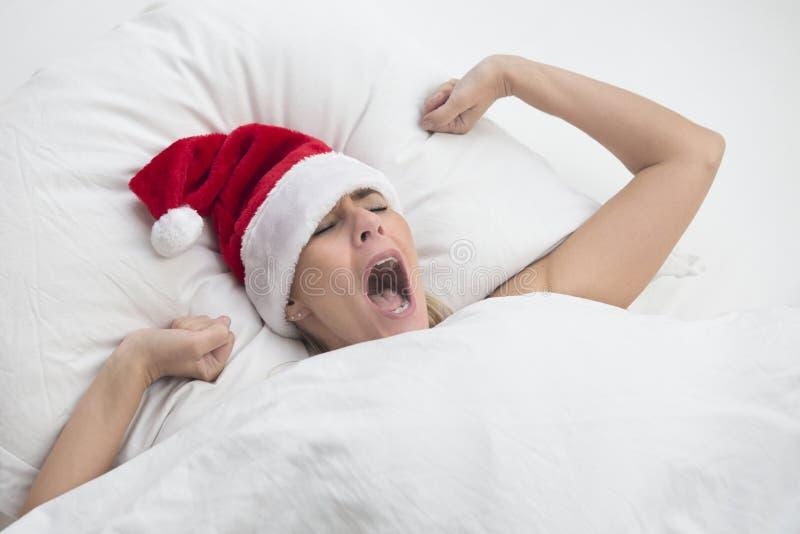 Donna a letto che sbadiglia con il cappello di Santa immagini stock libere da diritti