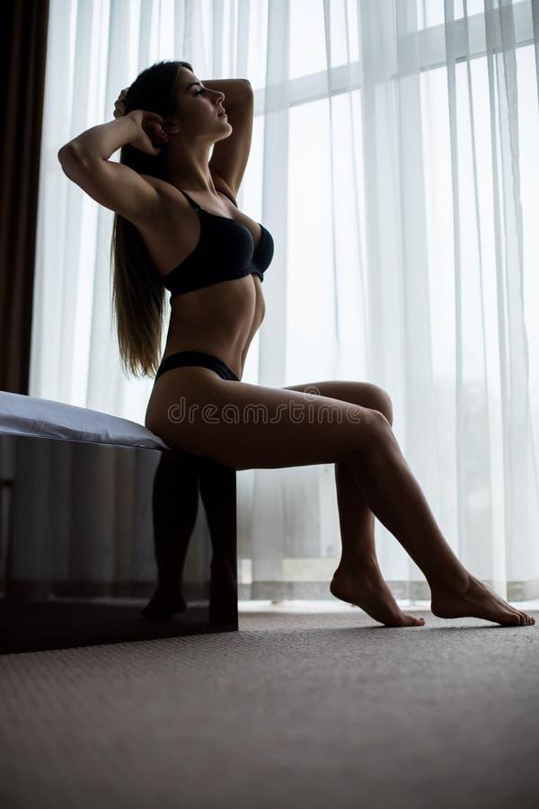 Donna a letto che sveglia mattina di vicino alla finestra immagine stock libera da diritti