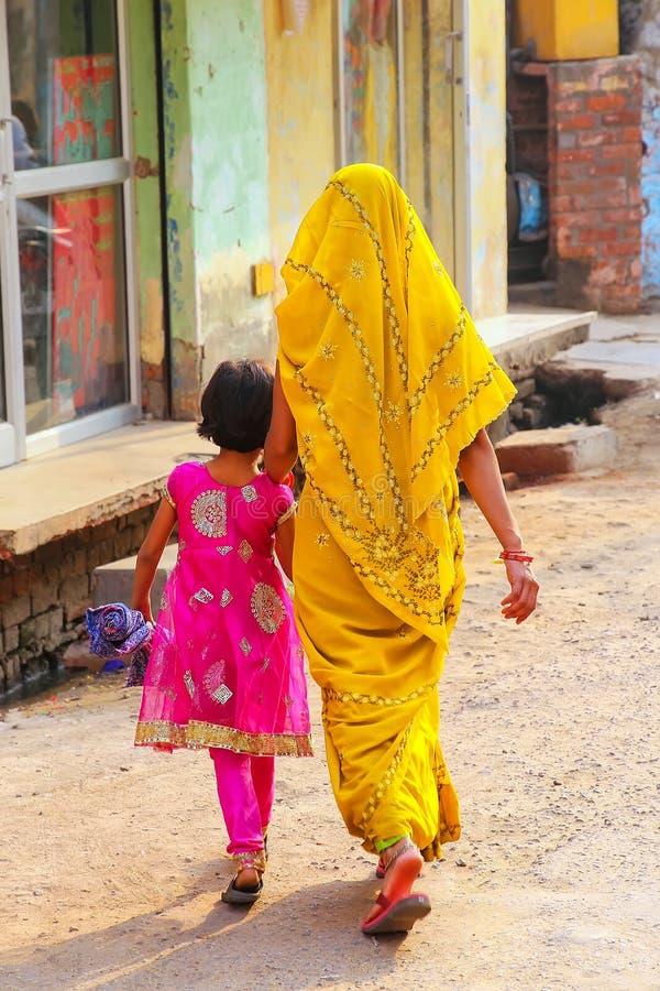 Donna locale con una ragazza che cammina nella via nel neighb di Taj Ganj fotografia stock libera da diritti