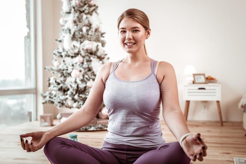 Donna luminoso dai capelli sorridente con la figura curvy che medita su pavimento di legno fotografia stock libera da diritti