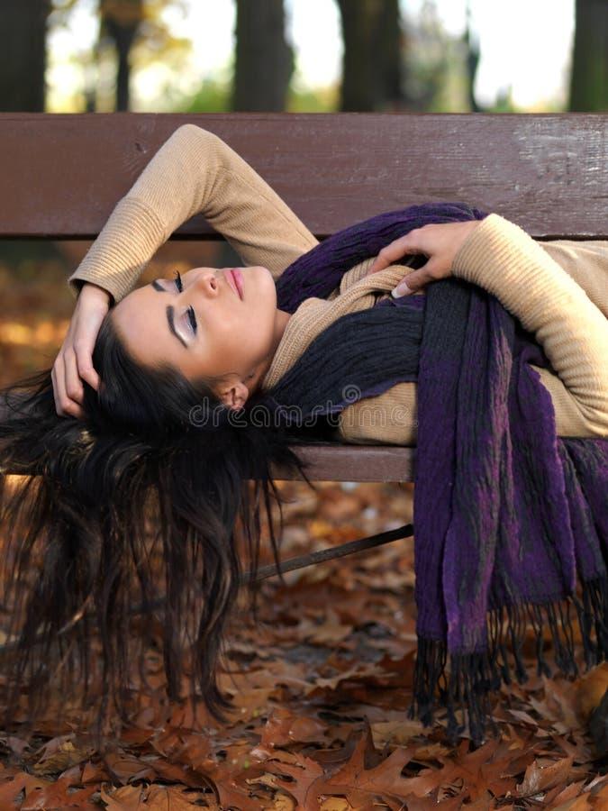 Donna lunga dei capelli che dorme sul banco in Autumn Outfit immagini stock