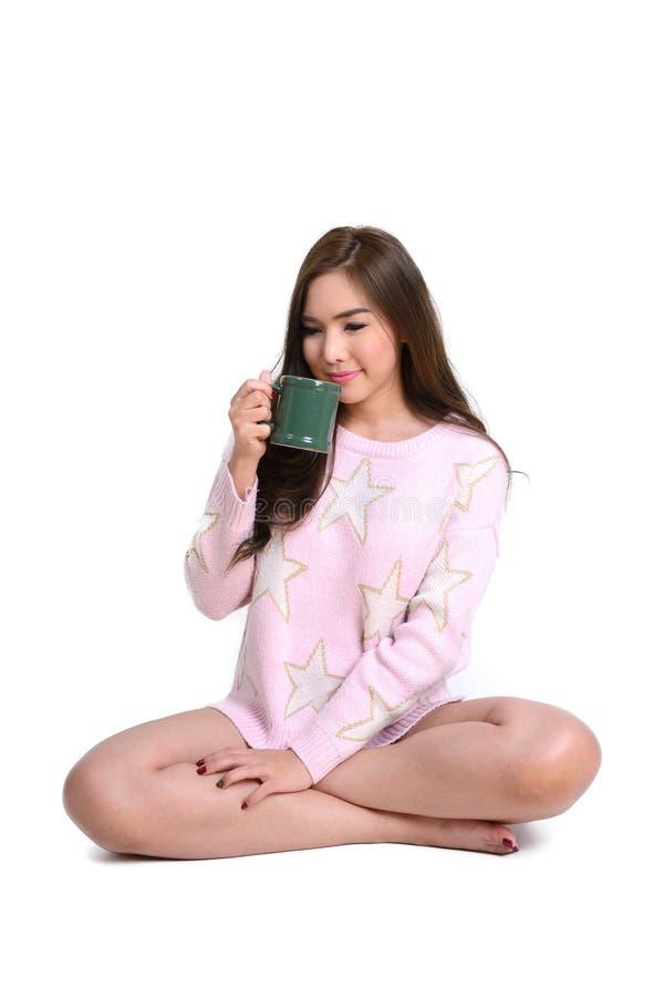 Donna lunga sveglia dei capelli in maglione rosa con la tazza da caffè verde fotografia stock