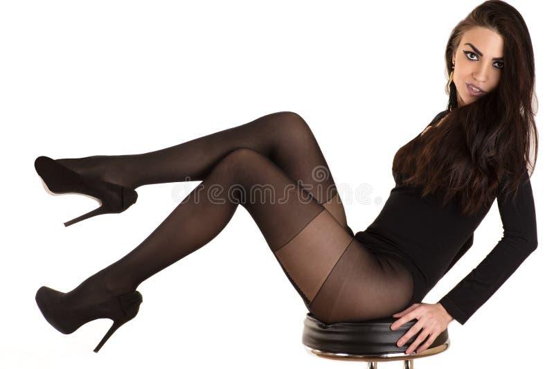 Donna lussuosa in calze che si siedono su una sedia fotografia stock