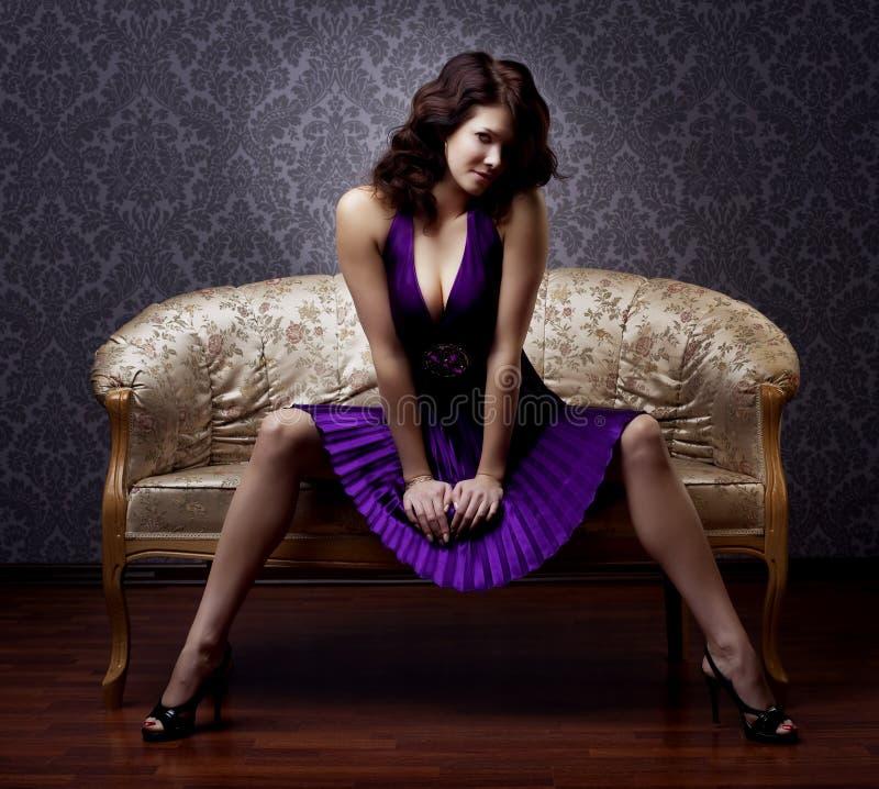 Donna lussuosa che si siede su uno strato dell'annata dell'oro fotografie stock