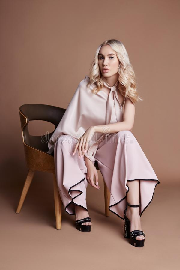 Donna lussuosa sexy in un vestito che si siede su una sedia Raccolta di autunno dell'abbigliamento delle donne Bionda di modo in  fotografia stock