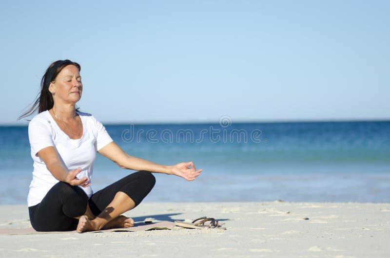 Donna maggiore attraente che meditating alla spiaggia fotografia stock