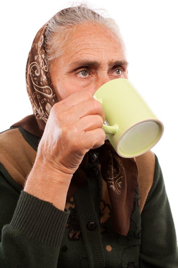 Donna maggiore che beve da una tazza fotografia stock libera da diritti