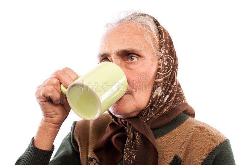 Donna maggiore che beve da una tazza fotografia stock