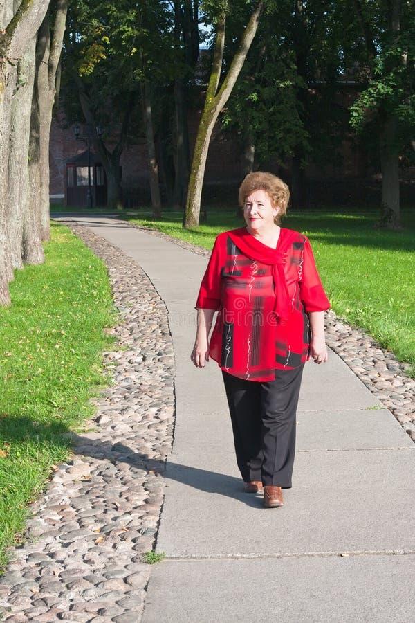 Donna maggiore che cammina all'aperto fotografia stock libera da diritti