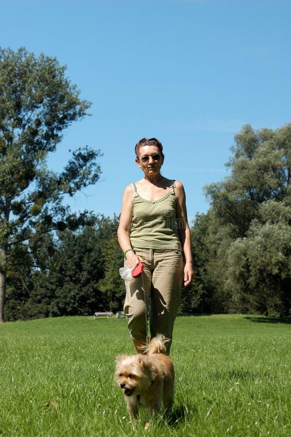 Donna maggiore che cammina il suo cane fotografia stock libera da diritti