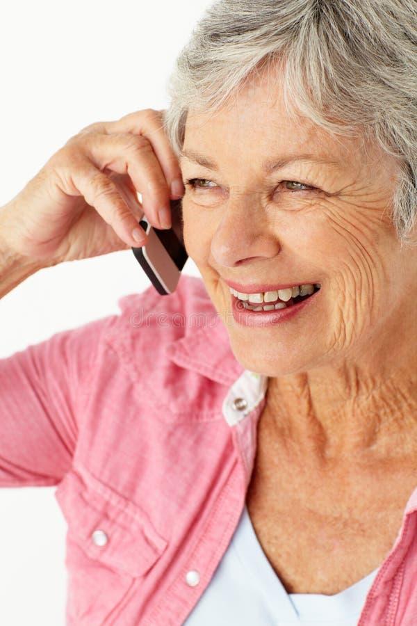 Donna maggiore che comunica sul telefono immagine stock