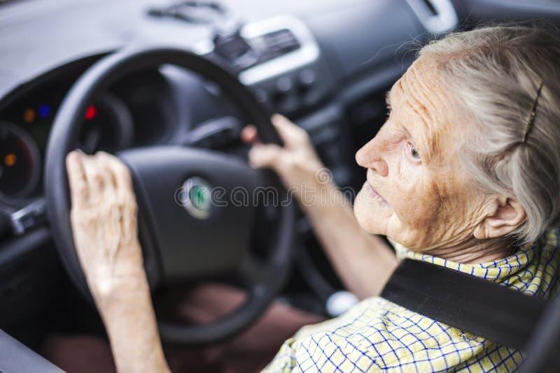 Donna maggiore che conduce un'automobile immagini stock