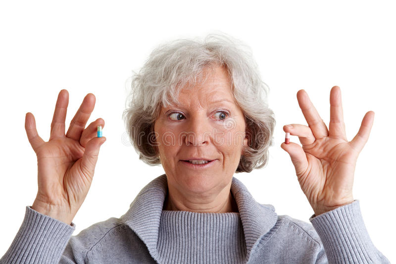 Donna maggiore che confronta due pillole fotografia stock
