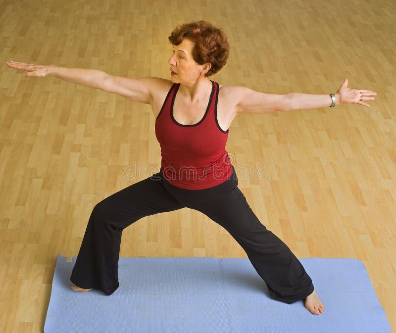 Donna maggiore che esercita yoga immagini stock