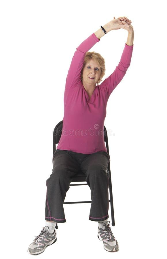 Donna maggiore che fa esercitazione di stirata in presidenza fotografia stock