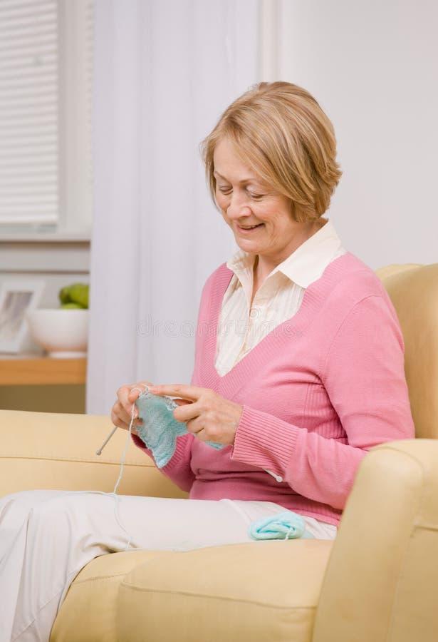 Donna maggiore che lavora a maglia sul sofà nel paese fotografia stock