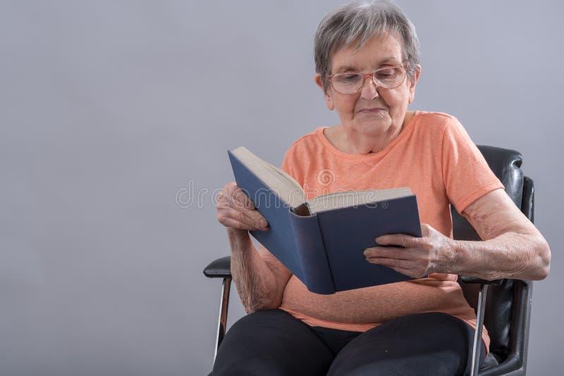 Donna maggiore che legge un libro fotografie stock libere da diritti