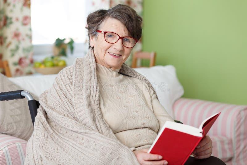 Donna maggiore che legge un libro fotografia stock