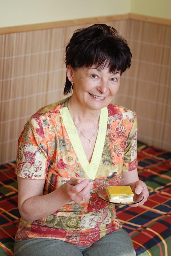 Donna maggiore che mangia torta fotografia stock