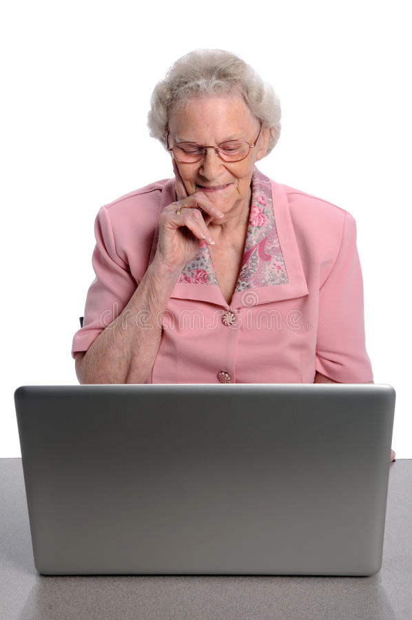 Donna maggiore che per mezzo del calcolatore fotografia stock