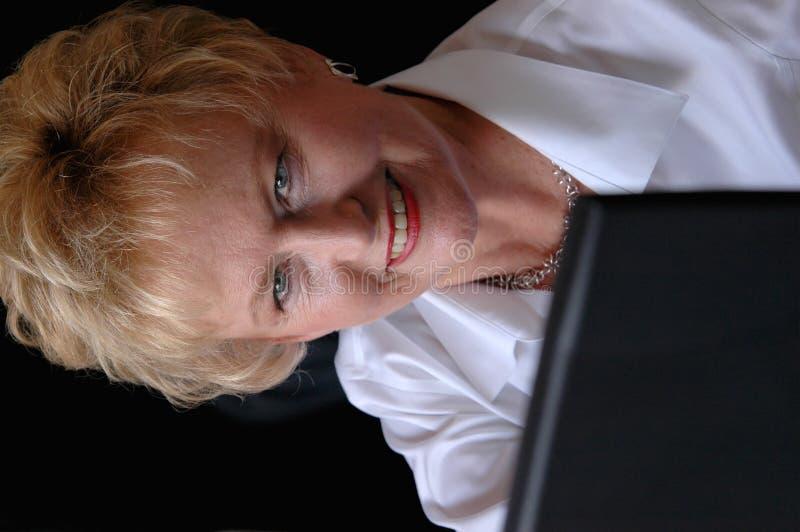 Donna maggiore che per mezzo del computer portatile fotografia stock