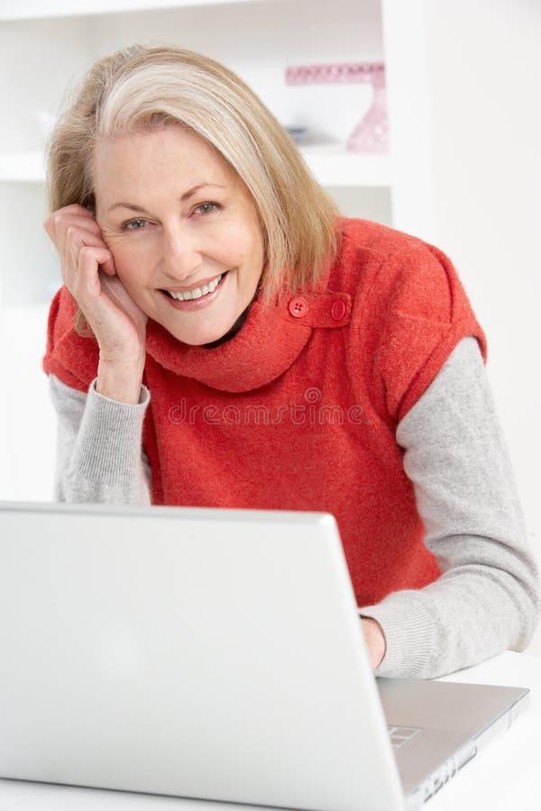 Donna maggiore che per mezzo del computer portatile nel paese fotografia stock