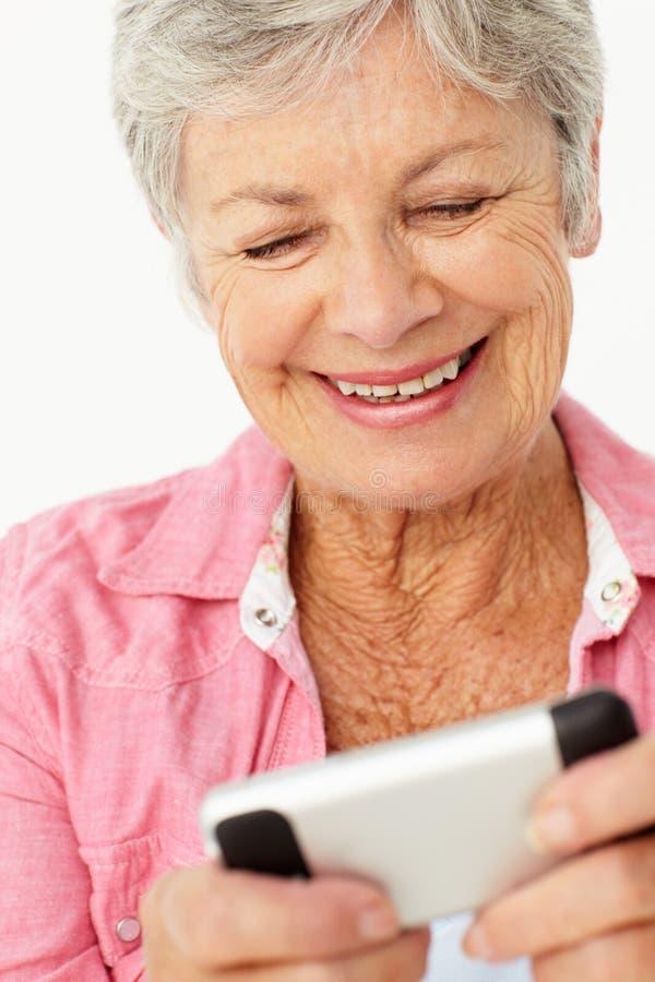 Donna maggiore che per mezzo del telefono mobile fotografia stock libera da diritti