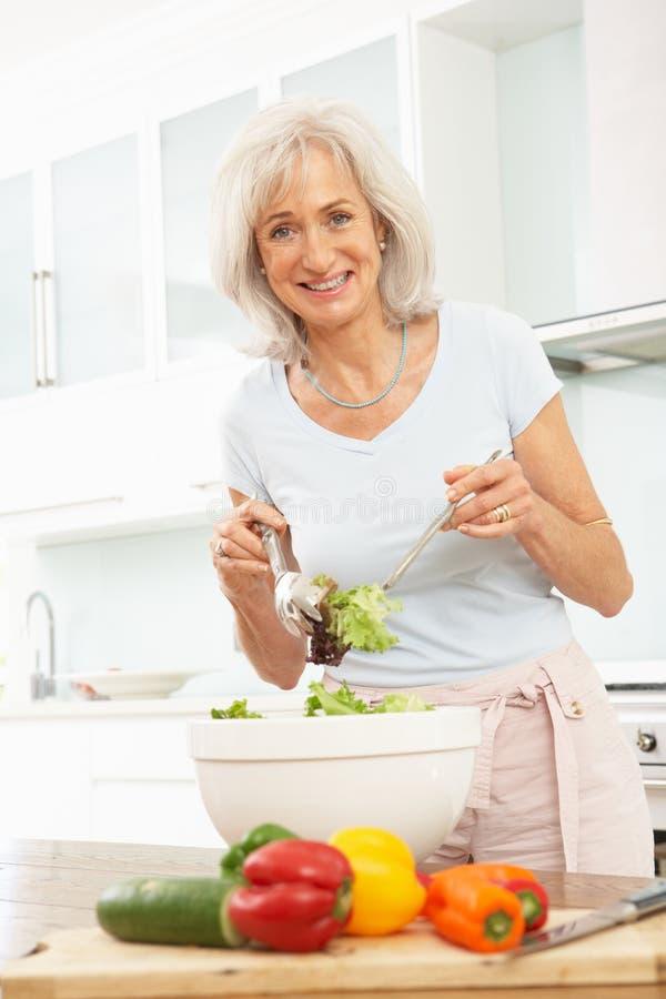 Donna maggiore che prepara insalata in cucina moderna immagini stock