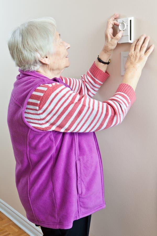 Donna maggiore che registra il suo termostato immagine stock
