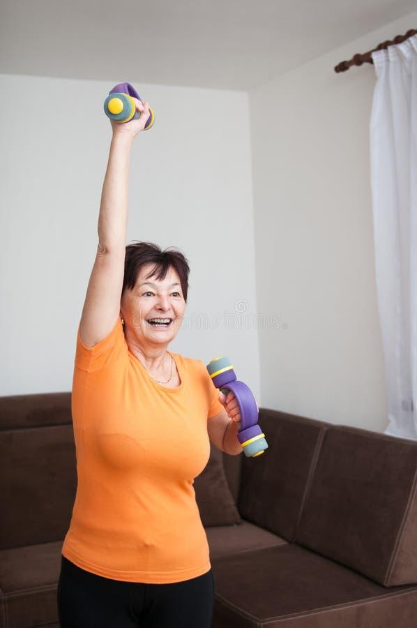 Donna maggiore che si esercita con i barbells fotografia stock