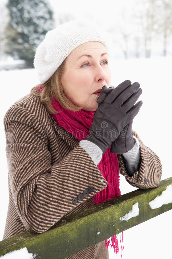 Donna maggiore che si leva in piedi in mani di riscaldamento della neve fotografie stock