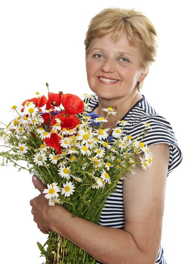 Donna maggiore che sorride con il mazzo di fiori selvaggi fotografia stock