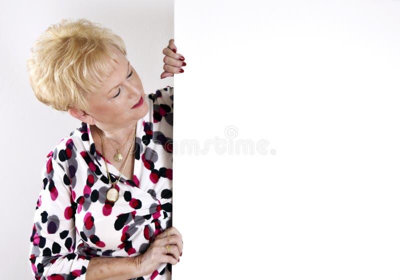 Donna maggiore che tiene segno bianco in bianco fotografie stock libere da diritti